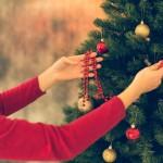 Frau schmückt den Weihnachtsbaum