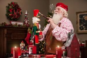 Ein Weihnachtsmann malt einen Nussknacker an