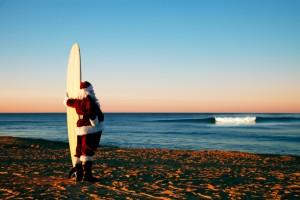Weihnachtsmann mit Surfbrett am Strand