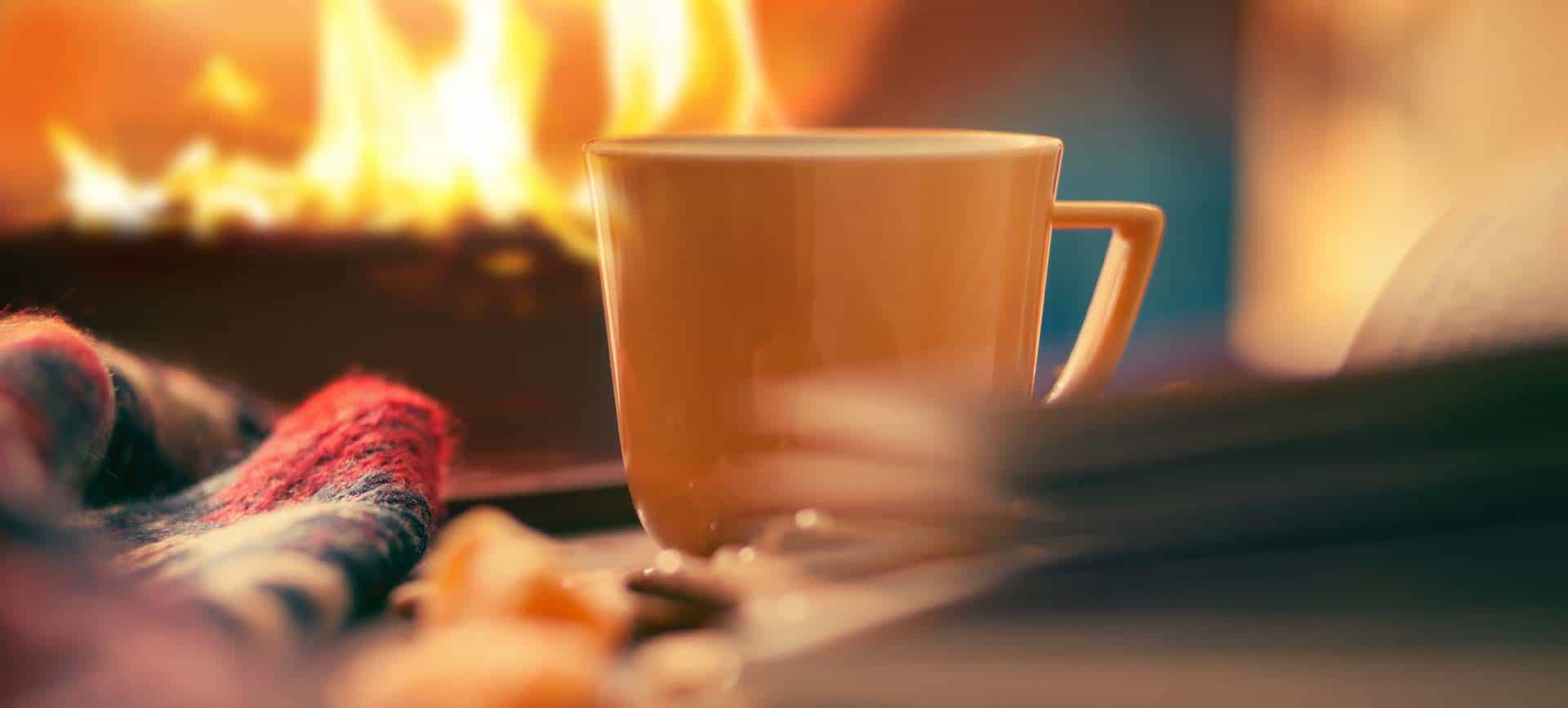 Tasse Tee vor Kaminfeuer
